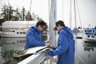 Sailing teammates fastening sail to boom - HEROF17077