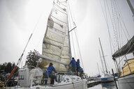 Sailing team preparing sailboat in harbor - HEROF17080