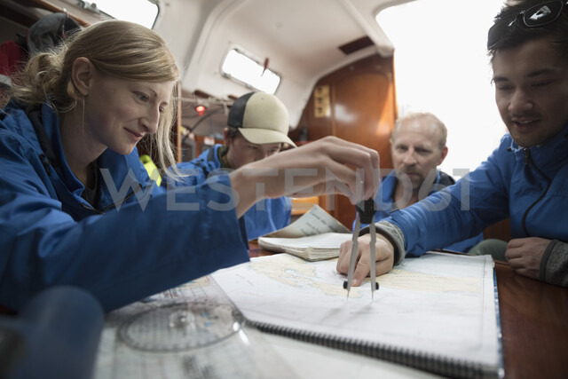 Sailing team plotting course at map on sailboat - HEROF17089 - Hero Images/Westend61
