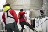 Sailing team adjusting rigging rope on sailboat - HEROF17110