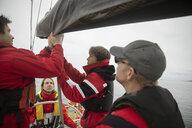 Sailing team adjusting sail on sailboat - HEROF17131