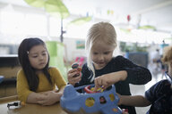 Preschool girls playing with airplane toy - HEROF17206