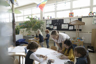 Preschool teacher and students using stencils on poster in classroom - HEROF17215