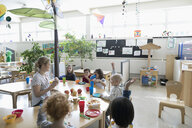 Preschool teacher and students eating during snack time in classroom - HEROF17245