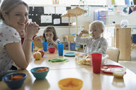Preschool teacher and students eating during snack time in classroom - HEROF17248