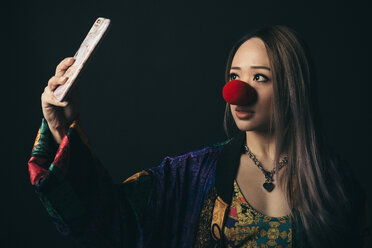 Renaissance portrait young female millennial wearing red clown nose, taking selfie with camera phone - HEROF17308