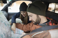 Adventurous couple checking map in truck - HEROF17365