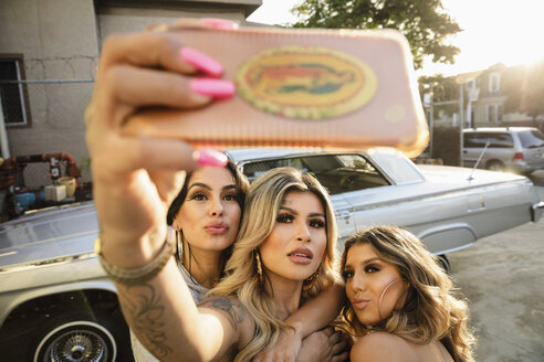 Latinx young women friends taking selfie with camera phone in front of low rider car in parking lot - HEROF17428
