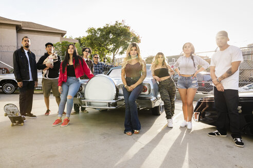 Portrait confident, cool Latinx friends in parking lot with vintage car - HEROF17452