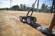 Man lining sunny baseball field - HEROF17488