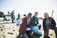 Beach cleanup volunteers picking up litter on sunny beach - HEROF17500