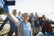 Beach cleanup volunteers taking selfie with camera phone - HEROF17503
