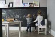 Brother and sister drawing on blackboard wall in playroom - HEROF17518