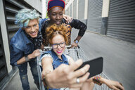 Cool young friends taking selfie with shopping cart in urban alley - HEROF17530