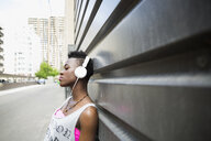 Cool young woman listening to music with headphones on urban street - HEROF17548