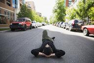 Cool young man laying on urban street - HEROF17581