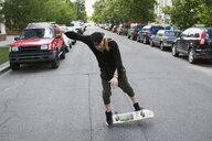 Cool young man skateboarding in urban street - HEROF17584