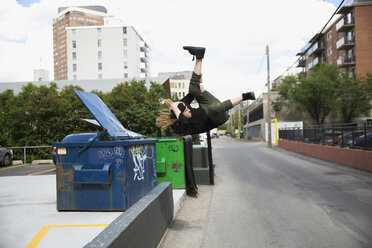 Cool young man doing parkour at dumpster in urban street - HEROF17587