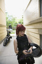 Cool woman with red hair and motorcycle helmet texting with cell phone in urban alley - HEROF17596