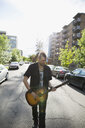 Cool man with mohawk playing guitar on urban street - HEROF17602
