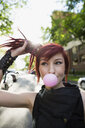 Cool woman with red hair blowing bubble gum on street - HEROF17605