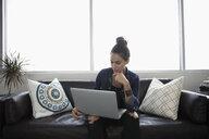 Woman using laptop on sofa - HEROF17629
