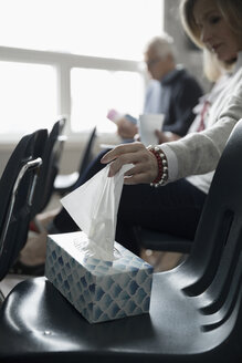 Woman reaching for tissue on chair at support group meeting in community center - HEROF17680
