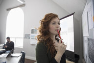 Thoughtful businesswoman brainstorming at whiteboard in office - HEROF17707