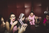 Young female millennial friends taking shots at bachelorette party at nightclub - HEROF17728