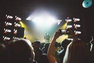 Woman with camera phone in crowd, videoing DJ on nightclub stage - HEROF17731