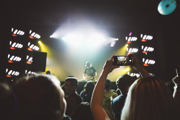 Woman with camera phone in crowd, videoing DJ on nightclub stage - HEROF17731