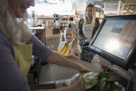 Worker helping mother and daughter at grocery store checkout - HEROF17758