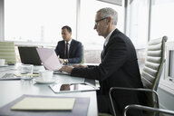 Businessmen working at laptops in conference room - HEROF17788
