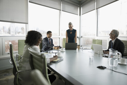 Businesswoman at laptop leading conference room meeting - HEROF17791