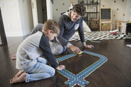 Father and son playing with track toy on floor - HEROF18064
