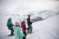 Family skiers skiing on snowy mountain - HEROF18106