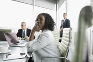 Confident, attentive businesswoman listening in conference room meeting - HEROF18127