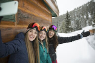 Enthusiastic female skier friends taking selfie with camera phone along snowy cabin - HEROF18280