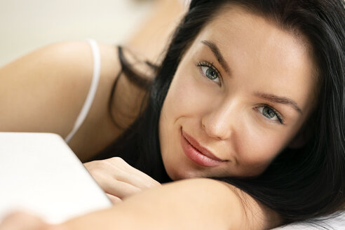 Portrait of a beautiful young woman, lying on bed - PESF01206
