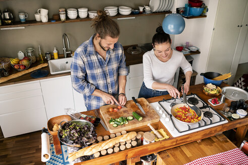 Young couple preparing food together, tasting spaghetti - PESF01227