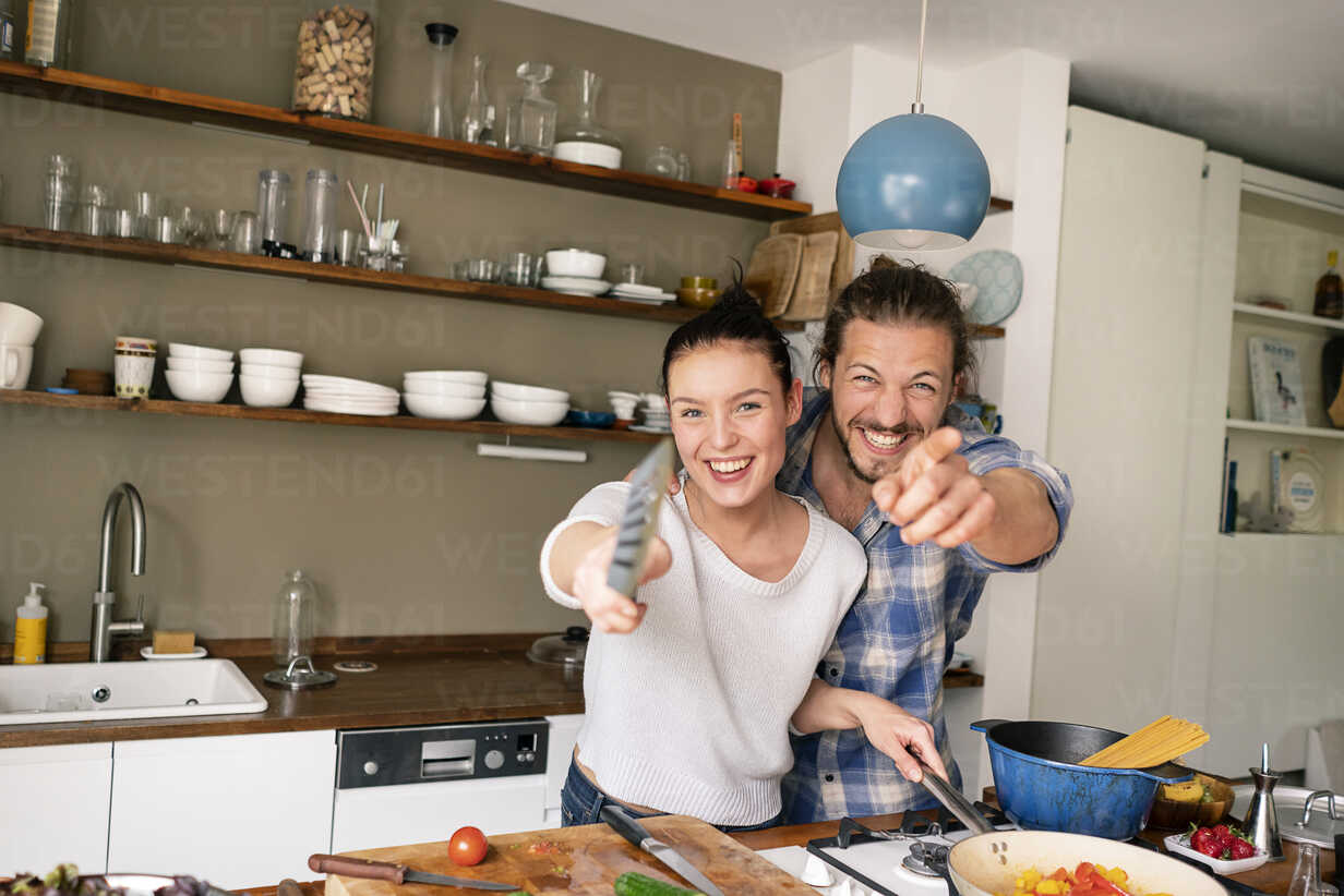 Young couple preparing food together, laughing and pointing with spatula - PESF01230 - Peter Scholl/Westend61