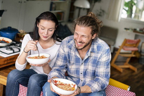 Happy couple sitting on kitchen table, eating spaghetti - PESF01245