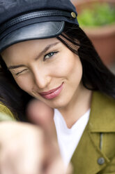 Portrait of a young woman with cap, winking and pointing - PESF01257