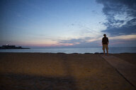 Italy, Sicily, Isola delle Correnti, Lido Scialai, man standing at the beach at dusk - MAMF00382