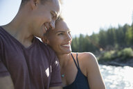 Affectionate couple hugging and smiling, sunny outdoors - HEROF18383