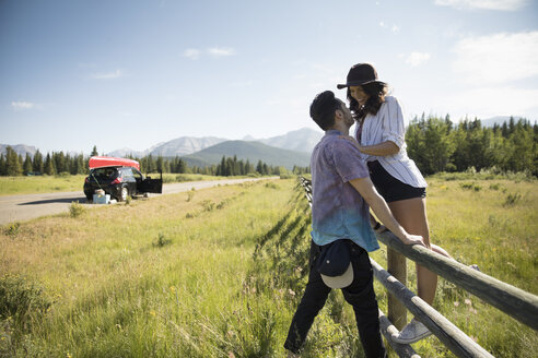 Affectionate young couple at fence on sunny summer rural roadside, enjoying road trip - HEROF18395