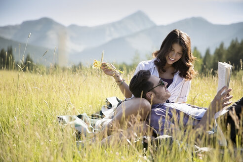 Affectionate young couple enjoying picnic and reading book in sunny summer rural field - HEROF18398