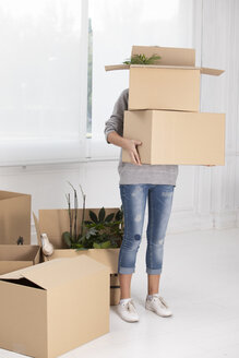 Unrecognizable woman carrying cardboard boxes in new home - ERRF00727