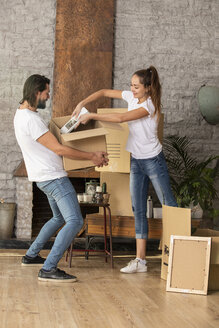 Couple packing cardboard box in new home - ERRF00739