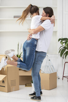 Happy couple with cardboard boxes hugging in new home - ERRF00751